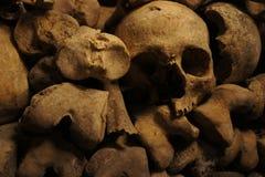 Un cráneo tuerto entre los huesos en las catacumbas de París Foto de archivo libre de regalías
