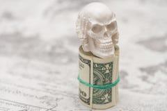 Un cranio che sta su un pacco di soldi, torto in un pacco Immagine Stock