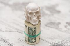 Un cranio che sta su un pacco di soldi, torto in un pacco Immagine Stock Libera da Diritti