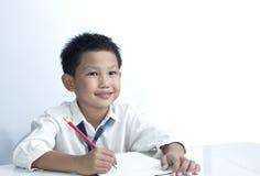 Un crayon heureux de fixation de garçon sur le fond blanc Image libre de droits