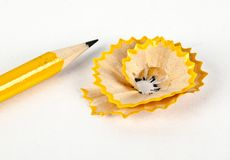Un crayon jaune avec des copeaux d'affûteuse et de crayon Photo stock