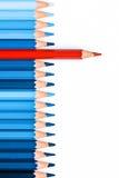Un crayon rouge parmi le bleu ceux d'isolement sur le fond blanc Photographie stock