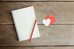 Un crayon sur un carnet et un coeur rouge avec le matin s'allument dans vi Photographie stock