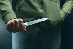 Un criminal con un arma del cuchillo amenaza matar Criminalidad, crimen, gamberro del robo fotografía de archivo