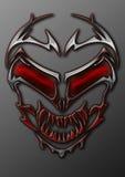 Un crâne étranger tribal en métal avec les yeux rouges rougeoyants Photo libre de droits