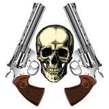 Un cráneo humano con dos revólveres de plata Imagen de archivo libre de regalías