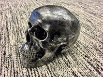 Un cráneo negro en una alfombra Imágenes de archivo libres de regalías