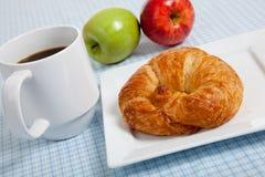 Un croissant con las manzanas y el café Foto de archivo libre de regalías