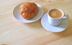Un croissant de beurre et une tasse de café chaud servie sur le Tableau en bois, avec l'espace de l'espace libre pour le texte Images libres de droits