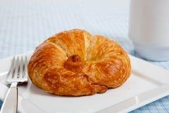 Un croissant en una placa blanca Fotografía de archivo libre de regalías