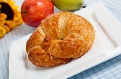 Un croissant en una placa blanca con las manzanas Imagen de archivo libre de regalías
