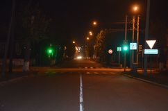 Un cruce en la noche imagenes de archivo