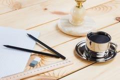 Un cuaderno abierto y una regla con dos lápices en un fondo de madera Cerca de la lámpara vieja y de una taza de café imagen de archivo libre de regalías