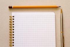 Un cuaderno ajustado en blanco con la pluma y el lápiz Fotografía de archivo