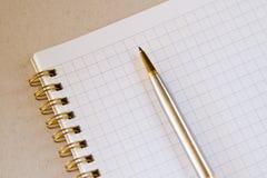 Un cuaderno ajustado en blanco con una pluma Imagen de archivo libre de regalías
