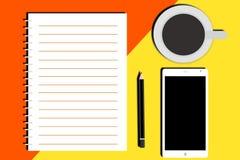 Un cuaderno, un café, un lápiz y un móvil en una tabla Imagen de archivo libre de regalías