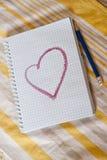 Un cuaderno con el corazón representado en una tabla Foto de archivo libre de regalías
