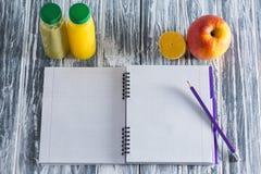 Un cuaderno con un lápiz, una manzana, jugos y una mitad de un limón en una tabla ligera de madera Imagen de archivo