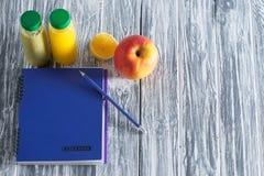 Un cuaderno con un lápiz, una manzana, jugos y una mitad de un limón en una tabla ligera de madera Espacio libre para la inscripc Foto de archivo libre de regalías