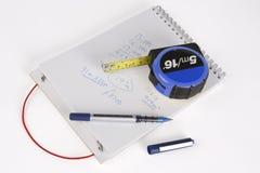 Un cuaderno de notas, una pluma y una cinta métrica foto de archivo libre de regalías