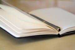 Un cuaderno en blanco abierto con una pluma, cierre para arriba Fotografía de archivo