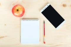Un cuaderno un teléfono y una manzana en la tabla Imagen de archivo libre de regalías