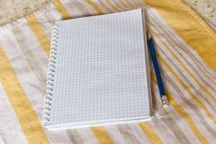 Un cuaderno y un lápiz en una toalla Fotos de archivo libres de regalías