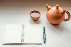 Un cuaderno y un teaset Fotografía de archivo