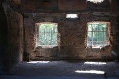 Un cuarto abandonado con una pared de ladrillo y dos ventanas con las barras Imagen de archivo libre de regalías