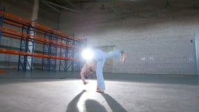 Un cuarto brillante Un hombre atlético que entrena a sus habilidades del capoeira y que realiza diversos tirones metrajes