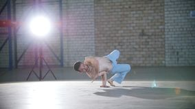 Un cuarto brillante Un hombre atlético que entrena a sus habilidades del capoeira y que se coloca en sus manos almacen de metraje de vídeo