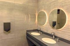 Un cuarto de baño con un lavabo y los espejos foto de archivo