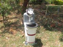 Un cubo de basura del mono hecho en broche del cierre del hormigón Foto de archivo