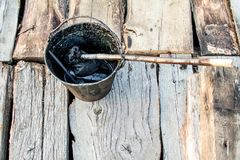 Un cubo de ebulliciones negras del alquitrán en el fuego para el uso en la reparación y la impermeabilización Foto de archivo libre de regalías