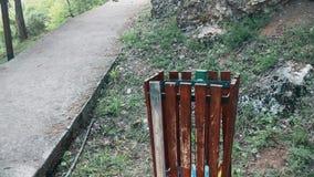 Un cubo de la basura limpio de madera al lado de la calzada peatonal en la montaña almacen de metraje de vídeo