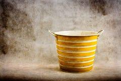 Un cubo rayado amarillo y blanco contra un marrón, fondo texturizado del metal Foto de archivo