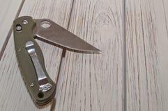 Un cuchillo plegable, abierto parcialmente en una tabla de madera blanca Fotografía de archivo libre de regalías