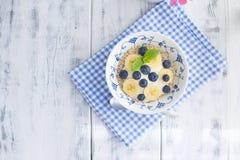Un cuenco de cereales con los arándanos y las frambuesas con el yogur en una tabla de madera, desayuno sano, fotografía de archivo