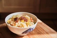 Un cuenco de chino Fried Rice con las salchichas y las verduras de cerdo foto de archivo libre de regalías