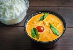 Un cuenco de curry de los pescados con las hojas de la albahaca y un cuenco de arroz hervido Imagen de archivo