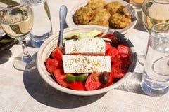Un cuenco de ensalada griega del pueblo al lado de bolas del calabacín platea y el vino blanco, vidrios de agua servidos en la ta Fotografía de archivo libre de regalías