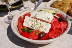 Un cuenco de ensalada griega del pueblo al lado de bolas del calabacín platea y el vino blanco, vidrios de agua servidos en la ta Imagen de archivo libre de regalías
