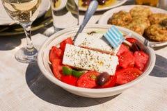 Un cuenco de ensalada griega del pueblo con la bandera griega encendido al lado de bolas del calabacín platea y el vino blanco, v Foto de archivo