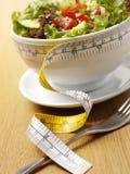 Un cuenco de ensalada mezclada con una cinta métrica Imagen de archivo