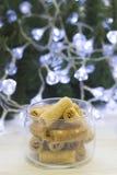 Un cuenco de galletas contra un árbol de navidad con las luces Foto de archivo