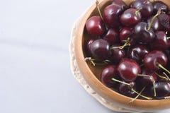 Un cuenco de madera llenado de las cerezas rojas Foto de archivo