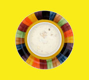Un cuenco de sopa de almejas en un fondo amarillo Imágenes de archivo libres de regalías