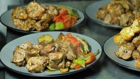 Un cuisinier fait à barbecue la viande et le boeuf juteux de poulet sur des plats avec des légumes cuits sur les charbons dans la photos stock