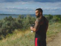 Un culturista bello muscolare con un tatuaggio sulla sua acqua potabile della spalla dopo un allenamento su uno sfondo naturale Fotografie Stock Libere da Diritti
