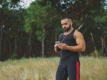 Un culturista bello muscolare con un tatuaggio sulla sua musica d'ascolto della spalla dopo un allenamento su uno sfondo naturale Fotografia Stock